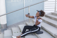 Smiling young woman sitting on stairs taking selfie with smartphone - JUNF01489