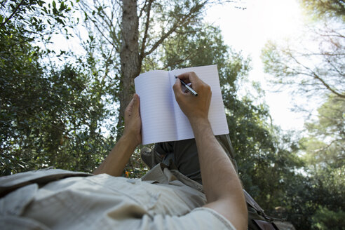 Man lying in hammock writing in notebook, partial view - JPTF00009
