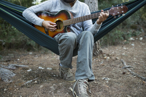 Man sitting in hammock playing guitar in the woods, partial view - JPTF00021