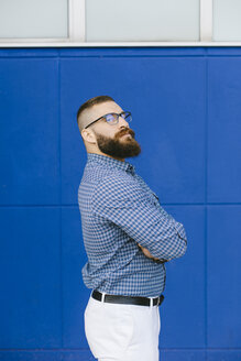 Portrait of bearded hipster businessman wearing plaid shirt standing in front of blue background - FMGF00015