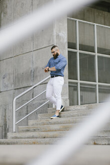 Bearded hipster businessman checking the time while walking downstairs - FMGF00018
