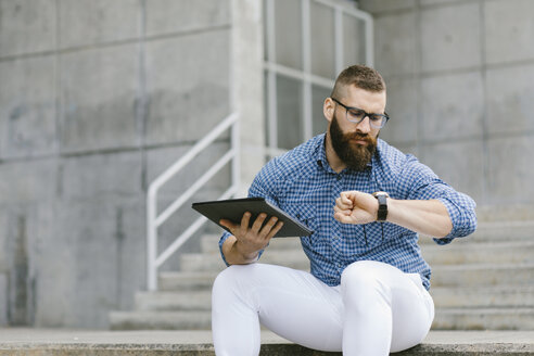 Portrait of bearded hipster businessman sitting on stairs with digital tablet checking the time - FMGF00024