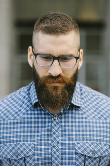 Portrait of bearded hipster businessman wearing glasses and plaid shirt - FMGF00033