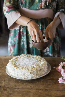 Young woman garnishing home-baked cake, partial view - ALBF00604