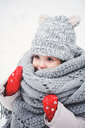 A cute baby girl in a knitted scarf and hat walking in the winter snow - INGF00026