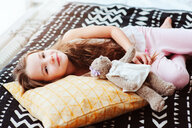 Portrait of a cute girl lying on her bed with her teddy - INGF00080