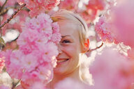 Close-up portrait of a woman posing with pink cherry blossoms - INGF00116