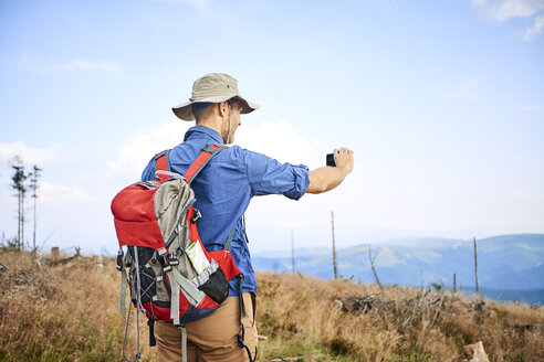 Man taking picture with his cell phone during hiking trip - BSZF00666