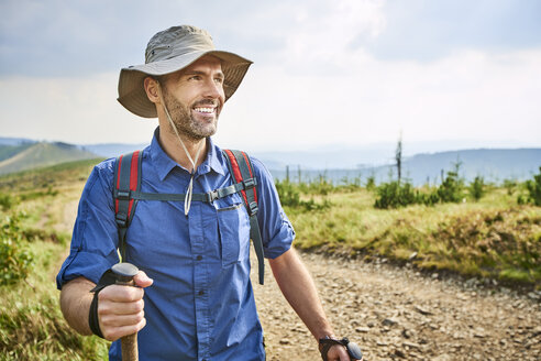 Portrait of smiling man hiking in the mountains - BSZF00669
