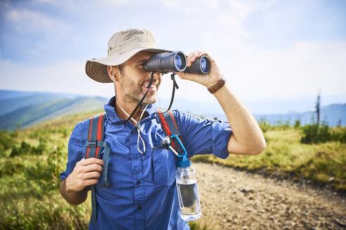Man looking through binoculars during hiking trip - BSZF00672