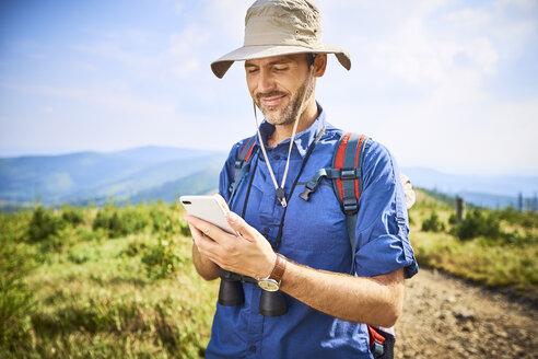 Smiling man checking his cell phone during hiking trip - BSZF00675