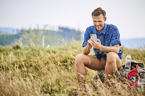 Smiling man resting and checking his cell phone during hiking trip - BSZF00681