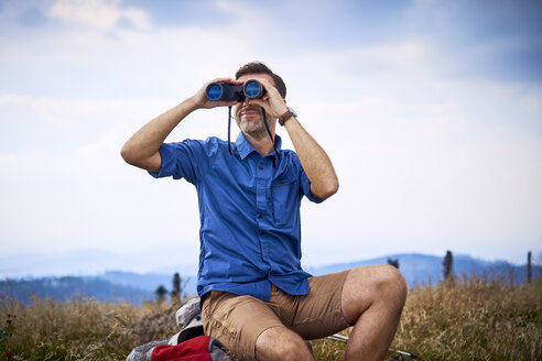 Man looking through binoculars during hiking trip - BSZF00684