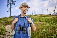 Smiling man with binoculars hiking in the mountains - BSZF00699