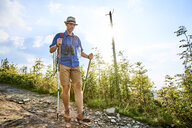 Man walking carefully with hiking poles on trail - BSZF00708
