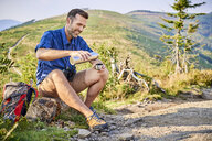 Smiling man resting during hiking trip pouring cold water from thermos flask - BSZF00714