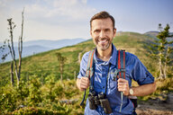 Portrait of smiling man hiking in the mountains - BSZF00717
