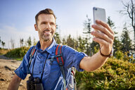 Man taking a selfie with his cell phone during hiking trip in the mountains - BSZF00720