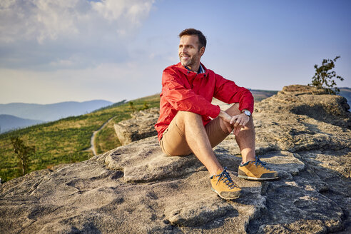 Man sitting on rock enjoying the view during hiking trip - BSZF00723