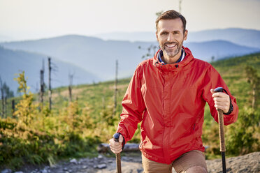 Portrait of smiling man hiking in the mountains - BSZF00726