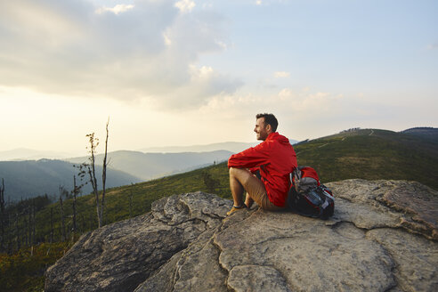 Man sitting on rock enjoying the view during hiking trip - BSZF00729
