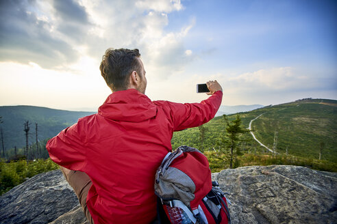 Man sitting on rock taking picture with his cell phone during hiking trip in the mountains - BSZF00732
