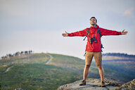 Man standing with outstretched arms on mountain top - BSZF00735