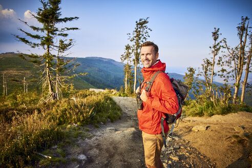 Portrait of smiling man hiking in the mountains - BSZF00738