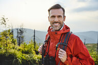 Portrait of smiling man hiking in the mountains - BSZF00741