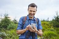 Smiling man checking his cell phone during hiking trip - BSZF00747