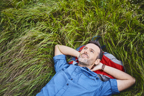 Relaxed man lying in grass enjoying hiking trip - BSZF00750