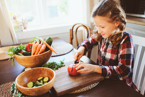 A young girl helping prepare a salad indoors - INGF00231