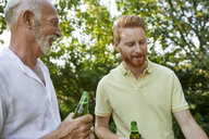 Senior father and adult son having a beer during barbecue in garden - ZEDF01580