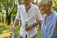 Senior couple having a barbecue in garden - ZEDF01595