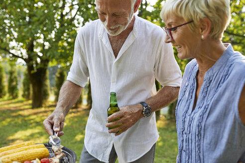 Senior couple having a barbecue in garden - ZEDF01595