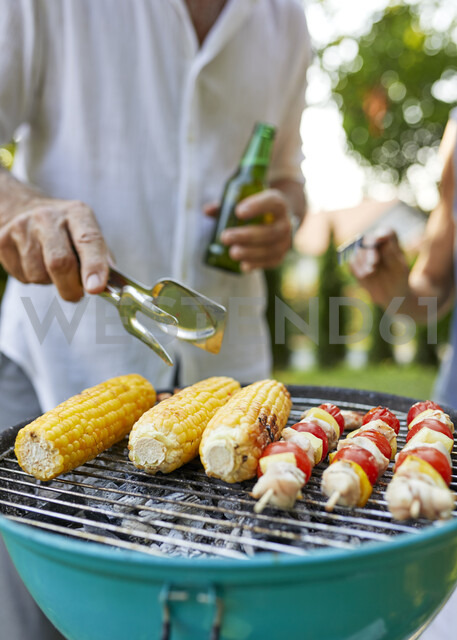 Corn cob and meat skewer on grill at barbecue in garden - ZEDF01598