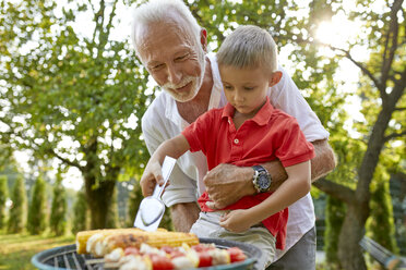 Grandfather helping grandson turning a corn cob during a barbecue in garden - ZEDF01601