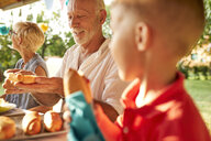 Senior man preparing a hot dog on a garden party - ZEDF01622