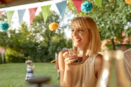 Happy woman drinking coffee on a garden party - ZEDF01649