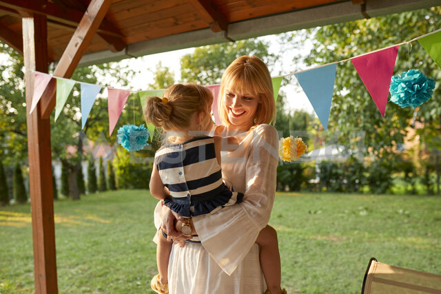 Happy mother carrying her daughter on a garden birthday party - ZEDF01655