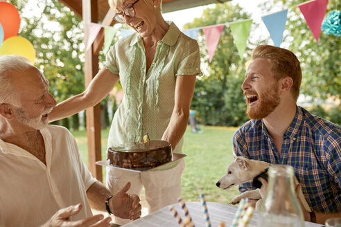 Happy woman handing over cake on a garden party - ZEDF01658