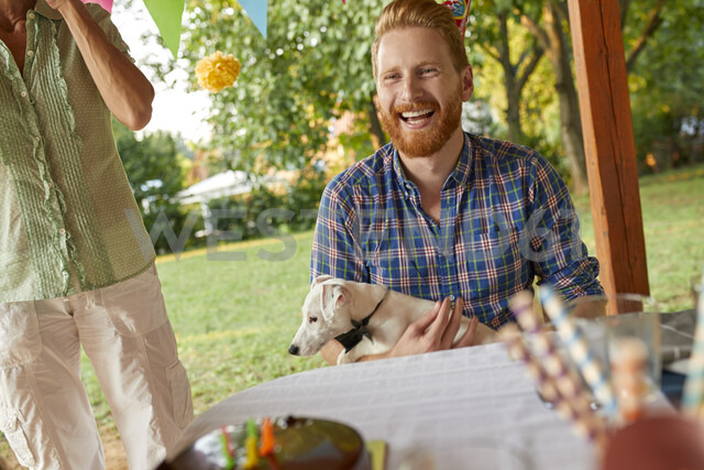 Happy man with dog on a garden party - ZEDF01673