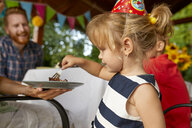 Little girl eating cake on a birthday garden party - ZEDF01676