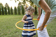 Grandmother and granddaughter playing together in garden with hoola hoop - ZEDF01682