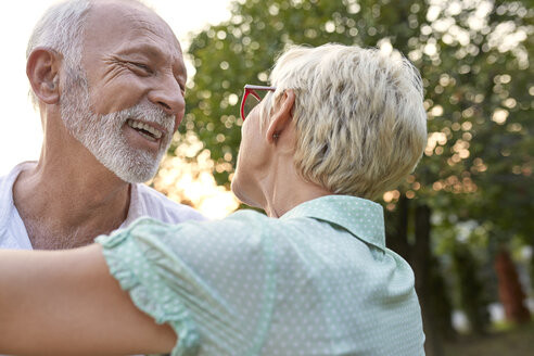 Happy senior couple hugging outdoors - ZEDF01685
