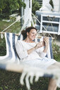 Smiling woman lying in a hammock using cell phone - HMEF00021