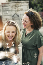 Two happy women with soap bubbles outdoors - HMEF00024