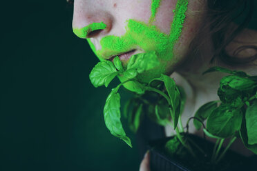 Close-up portrait of a young woman with green paint on her face next to a green plant - INGF00364