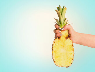Studio shot of a human hand holding a pineapple against a blue background - INGF00406