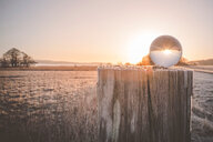 A spherical ball on a wooden post in the sunlight in Scandinavia - INGF00442